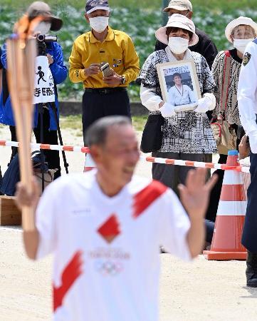 佐賀県みやき町の聖火リレー会場で、ランナーの寺田恭夫さんを見つめる古賀稔彦さんの母愛子さん(奥右から2人目)=10日午前