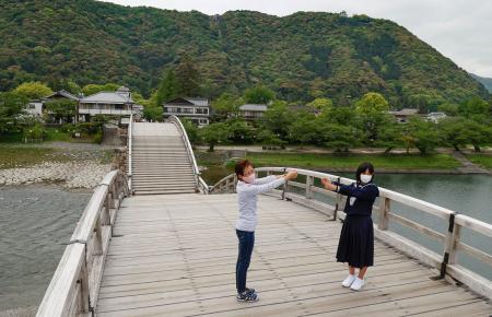 聖火リレーのルートとなっていた錦帯橋でトーチキスのポーズをする三浦由子さん(左)=13日午後、山口県岩国市