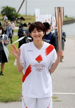 山口県宇部市を走り終え、観客に手を振る聖火ランナーの宝来麻紀子さん=14日午前
