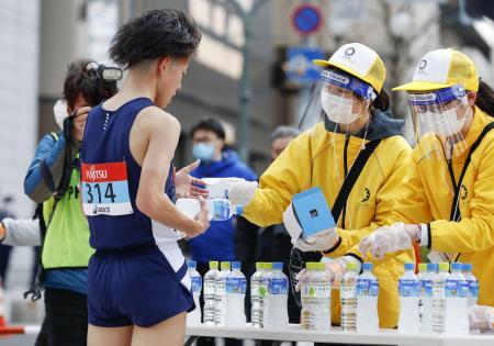 東京五輪のテスト大会となる「札幌チャレンジ10キロ」で、ゴールした選手にマスクを手渡すスタッフ=5日、札幌市
